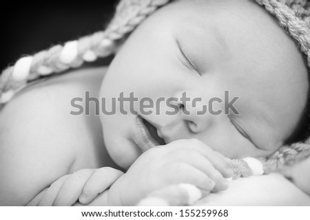 Newborn peacefully asleep black and white - stock photo