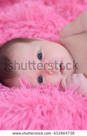 Newborn portrait, baby girl lying on pink background looking at camera.