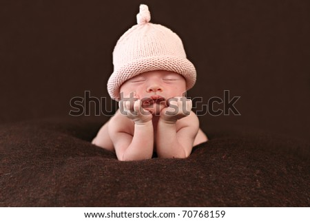 Newborn  propped up with head on hands - stock photo
