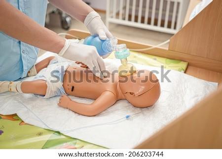 newborn resuscitation on a mannequin - stock photo