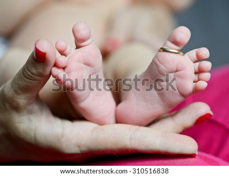 newborn's foot in the mother hand with wedding ring on finger - stock photo