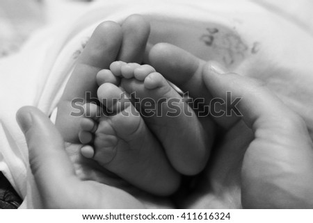 Newborn's legs in father's hands