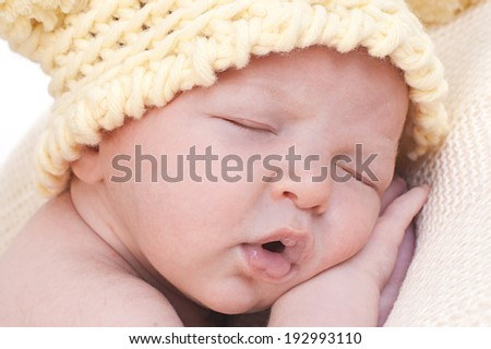 Newborn sleeping baby in knitted yellow hat - stock photo