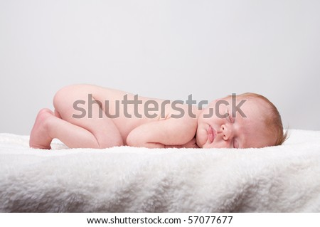 Newborn sleeping child on white blanket - stock photo