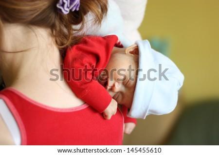 Newborn sleeping on mother's shoulder - stock photo