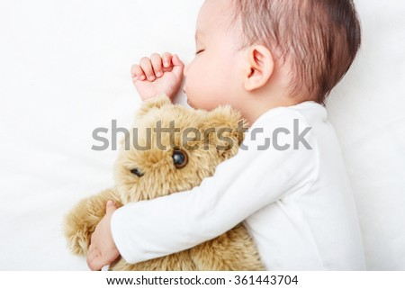 Newborn sleeping with her teddy bear, new family and love concept (Soft focus and blurry) - stock photo