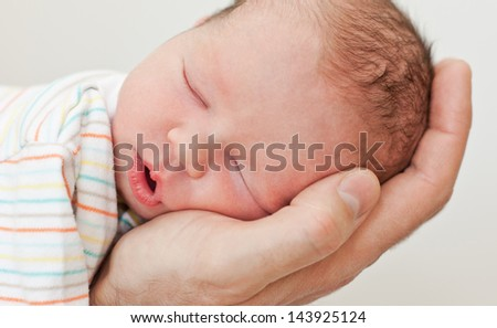 newborn sleeps on a hand on a white background - stock photo