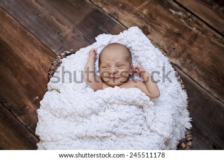 Newborn smiling baby sleeping in a wooden basket  - stock photo