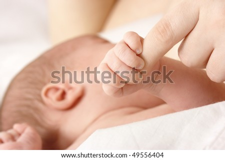 Newborn sucks mother's breast and grips her finger, breastfeeding, shallow DOF