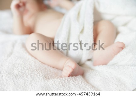 newborn tiny baby lying on the bed with blanket