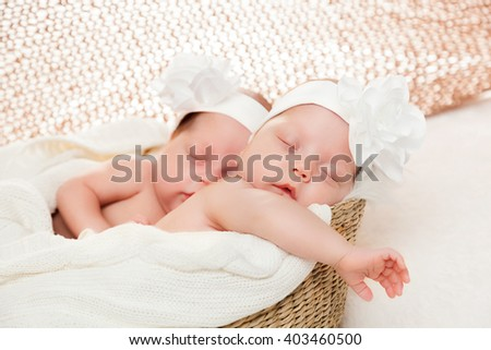 Newborn twins sisters sleeping in basket and hugging each other, wearing white headband - stock photo