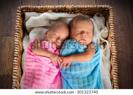 Newborn twins sleeping inside the wicker basket - stock photo