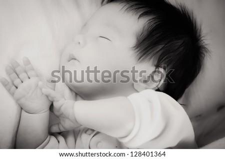 Newborn with dark hair and open hands sleeping - stock photo
