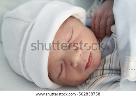 newborn with hours sleeping in the hospital with a hat