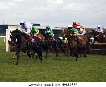 NEWBURY, BERKS; MAR 27:  jockeys jostle for position over hurdles in the 3rd race at Newbury Racecourse, UK, March 27, 2010 in Newbury, Berks - stock photo