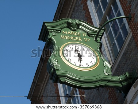 Newbury, Northbrook Street, Berkshire, England - December 22, 2015: Marks and Spenser clock sign over shop entrance, company founded in 1884 by Michael Marks and Thomas Spenser - stock photo