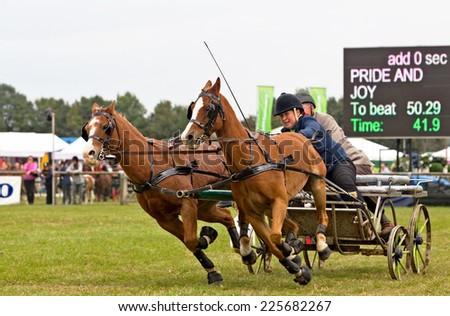 NEWBURY, UK - SEPTEMBER 21: An unnamed driver & passenger propel their scurry race rig around the course at speed attempting to set the fastest time at the Berks show on September 21, 2014 in Newbury
