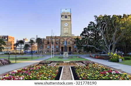 newcastle Australia ?own hall facade from park with blooming flowers during reconstruction of clock tower - stock photo