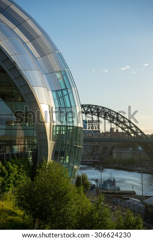 NEWCASTLE, ENGLAND - AUGUST 6, 2015: Sage Gateshead, a concert hall on Newcastle/Gateshead Quayside.  Located on the south bank of the River Tyne.  Rugby World cup 2015 ad can be seen on Tyne Bridge.