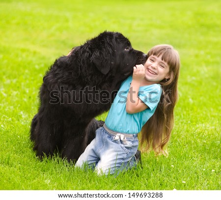 Newfoundland dog kisses a girl - stock photo