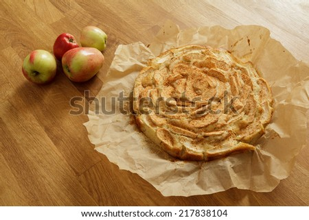 Newly baked apple pie on baking paper with apples lying next to it - stock photo