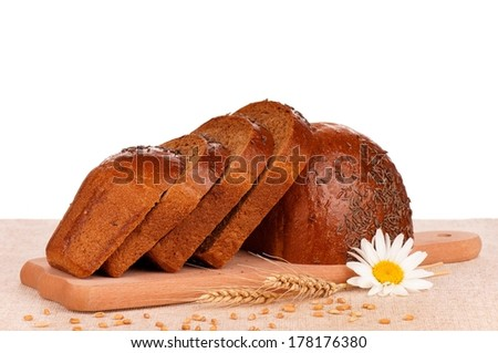 Newly-baked rye bread on the cutting board over white background - stock photo