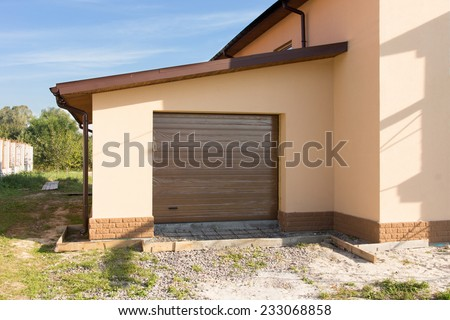 Newly built single garage with a closed roll up door annexed to the edge of a new house construction - stock photo