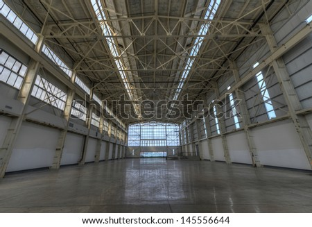 Newly constructed empty warehouse/factory during the day, filled with natural light.