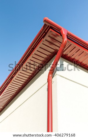 newly installed red rain gutter and drainpipe - stock photo