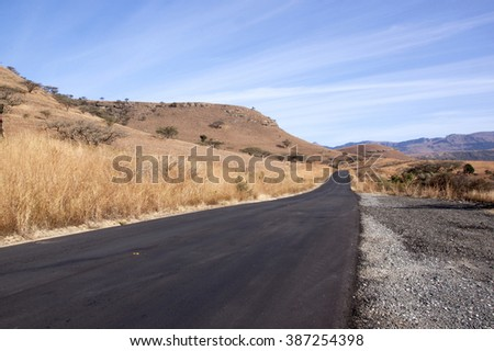 Newly laid asphalt road in dry South African rural landscape - stock photo