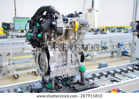 Newly manufactured engine on the production line in a factory. Behind the engine is computer on the desk. - stock photo