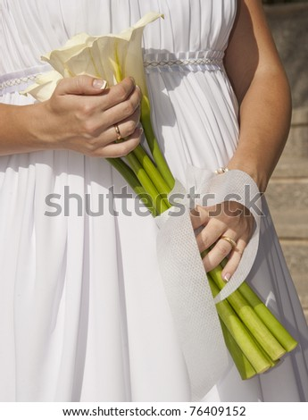 Newly married bride holding a bunch of flowers with rings on fingers