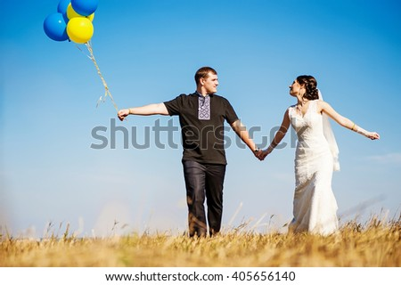 Newly married couple in field - stock photo