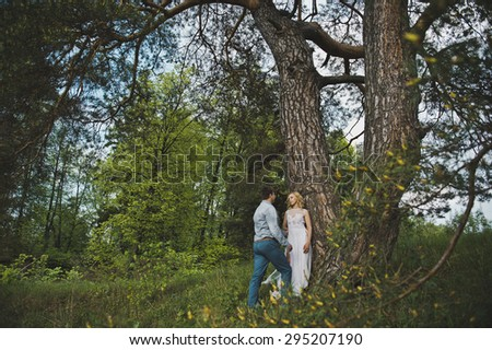 Newly-married couple in the wood about a tree.