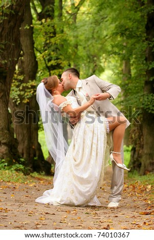 Newly-married couple kisses on a wood lawn - stock photo