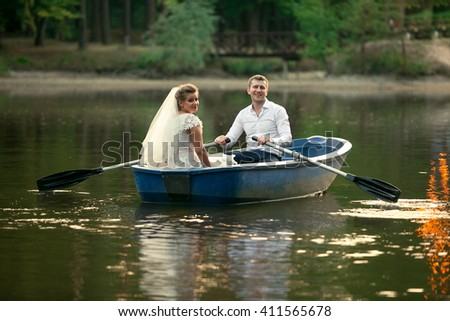 Newly married couple riding on old wooden boat on lake - stock photo