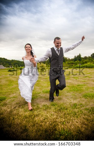 Newly married couple running and jumping in park while holding hands - stock photo