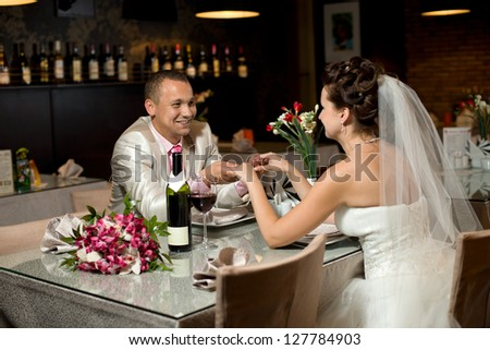newly married couple sit at table in restaurant,  romance wedding dinner