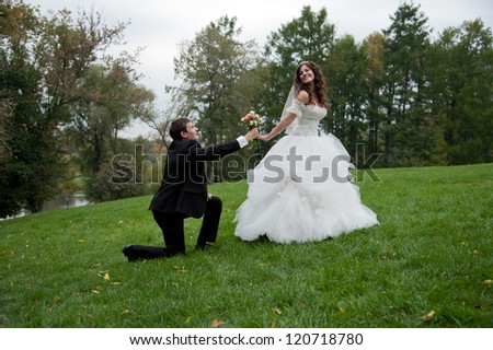 Newly married couple stands in field. Outdoor portrait of bride and groom