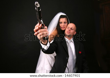 newly-married couple with gun - stock photo