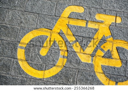Newly painted yellow bycicle road sign marking on modern  gray cobblestone pawement background image - stock photo