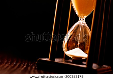 Newly turned hourglass with running sand measuring the passing time to a deadline or expiry of a fixed time period, close up on a dark background - stock photo