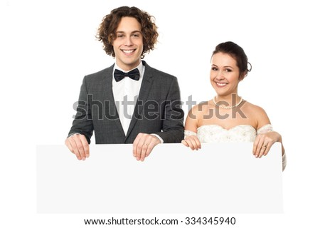 Newly-wed couple displaying a blank poster - stock photo
