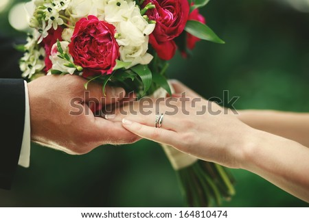 Newly wed couple holding hands, groom and bride together on wedding day. - stock photo