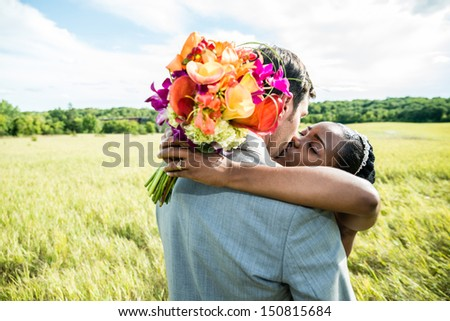 Newly wed couple kissing on a grass field - stock photo