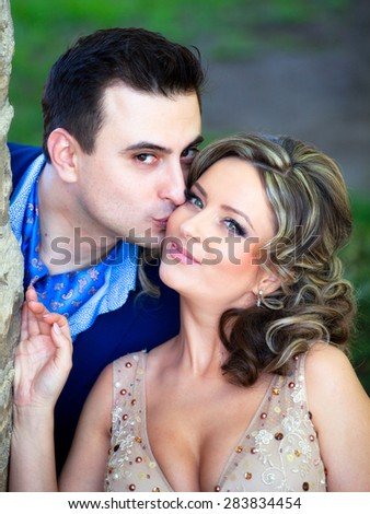 Newly wed couple kissing outdoor on a summer day.