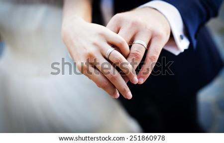 Newly wed couple's hands with wedding rings - stock photo