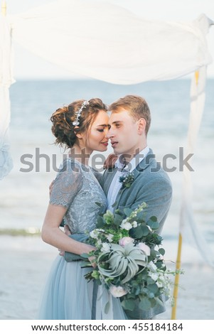 Newly-weds cuddling at the seashore.