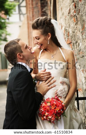 newly weds showing tongues to each other - stock photo