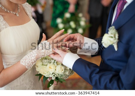 Newlywed bride and groom exchanging golden wedding rings at ceremony - stock photo